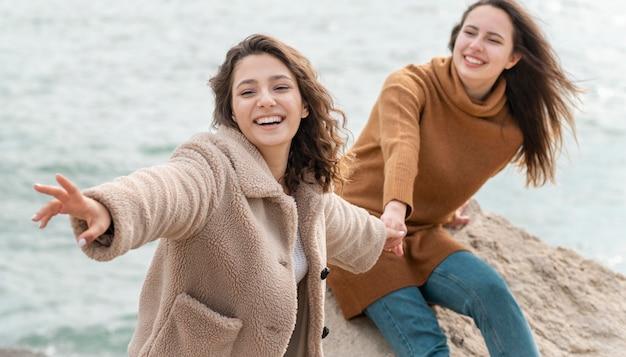 Mujeres felices posando juntos tiro medio