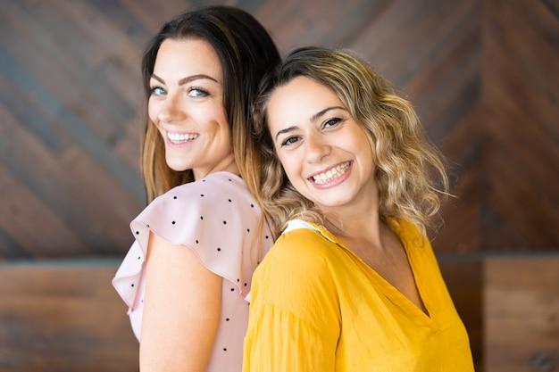 Mujeres felices posando y mirando a la cámara
