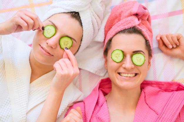 Mujeres felices con rodajas de pepino en los ojos