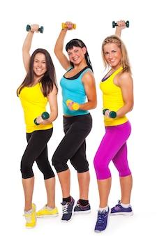Mujeres felices en ropa deportiva con pesas