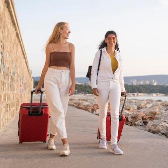 Mujeres felices de tiro completo con equipaje