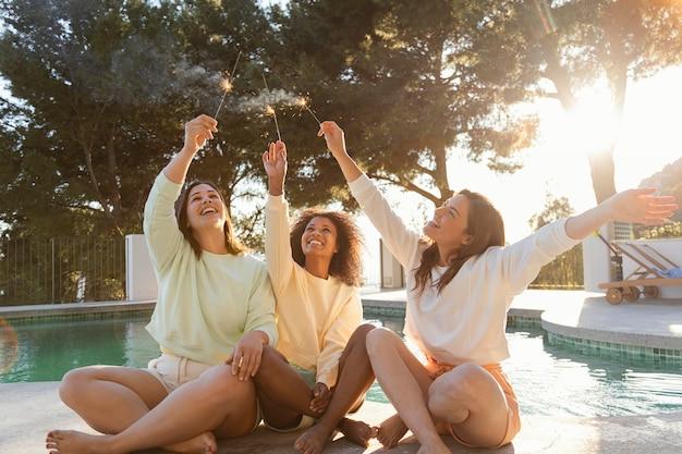 Mujeres felices con tiro completo de fuegos artificiales