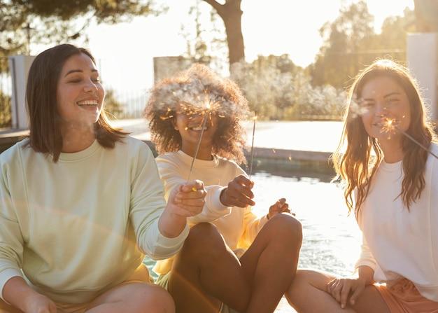 Mujeres felices con tiro medio de fuegos artificiales