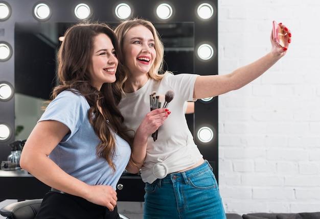 Mujeres felices tomando selfie en espejo de maquillaje