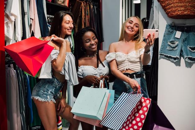 Mujeres felices tomando selfie en tienda