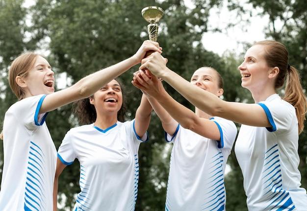 Mujeres felices con vista lateral de la copa de oro