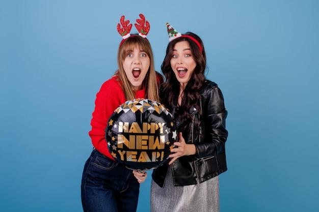 Mujeres con feliz año nuevo globo vistiendo ropa de invierno
