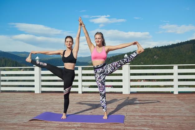 Las mujeres flexibles que hacen de la mano a los pies posan juntas al aire libre.