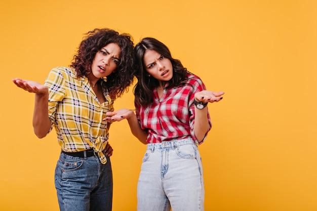 Mujeres frustradas en jeans miran inquisitivamente, extendiendo los brazos a los lados. retrato de niñas con rizos