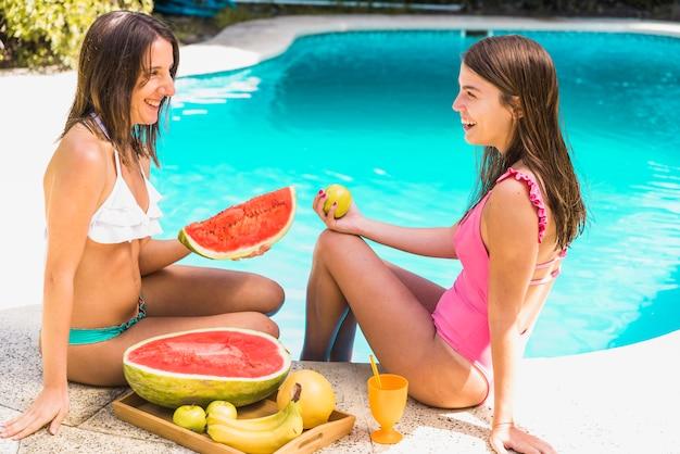 Mujeres con frutas tropicales sentadas junto a la piscina.