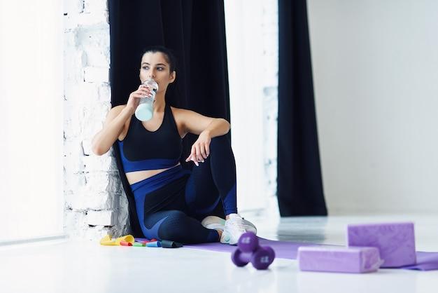 Mujeres fuertes en ropa deportiva sentada en una estera de yoga y bebiendo agua después del entrenamiento en casa