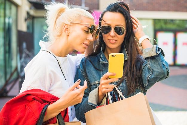 Mujeres en gafas de sol mirando smartphone