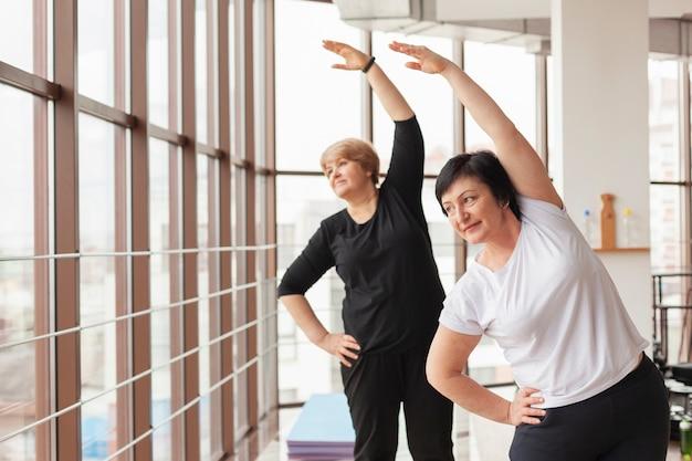 Mujeres en el gimnasio estirando