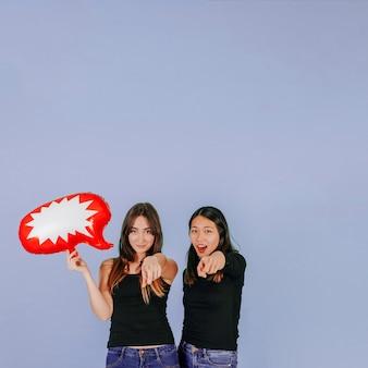 Mujeres con globo de discurso apuntando a la cámara