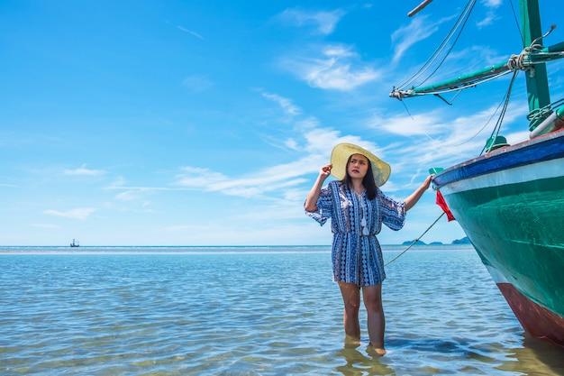 Mujeres y grandes sombreros viajan al mar en verano.