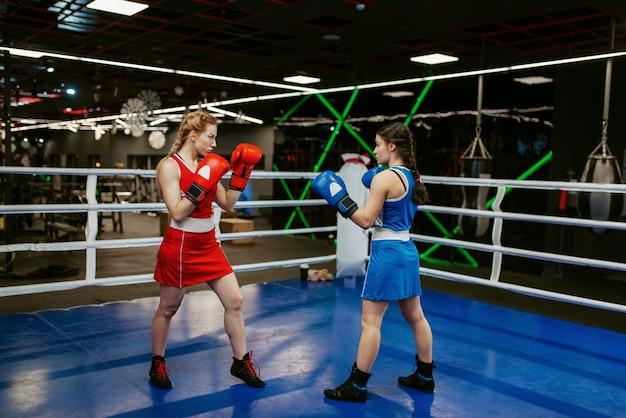 Mujeres en guantes de boxeo en el ring, entrenamiento de caja