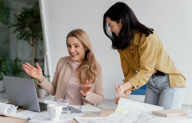 Mujeres hablando de un proyecto en una reunión.