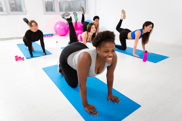 Mujeres haciendo ejercicio en la colchoneta en el gimnasio