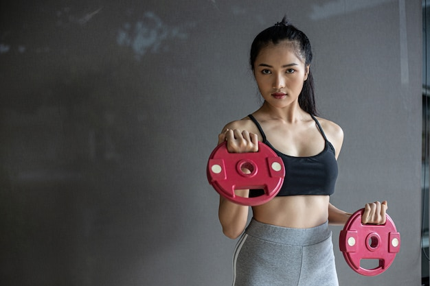 Mujeres haciendo ejercicio con dos pesas con mancuernas