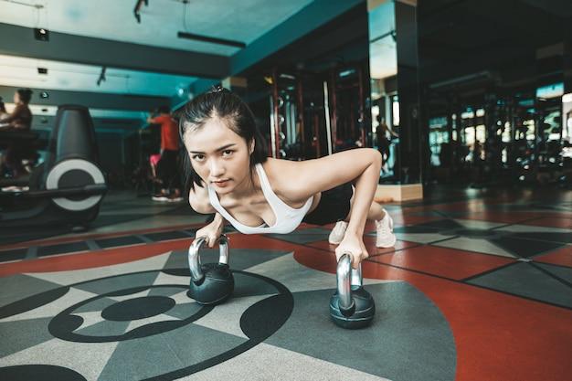 Mujeres haciendo ejercicio empujando el suelo con el kettlebell en el gimnasio.