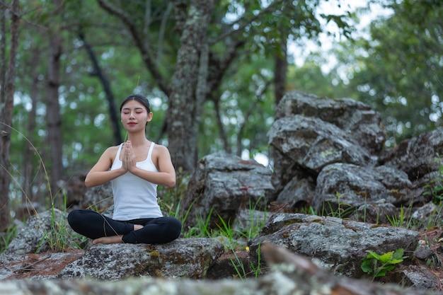 Mujeres haciendo ejercicio, haciendo yoga en el parque, día mundial del yoga.