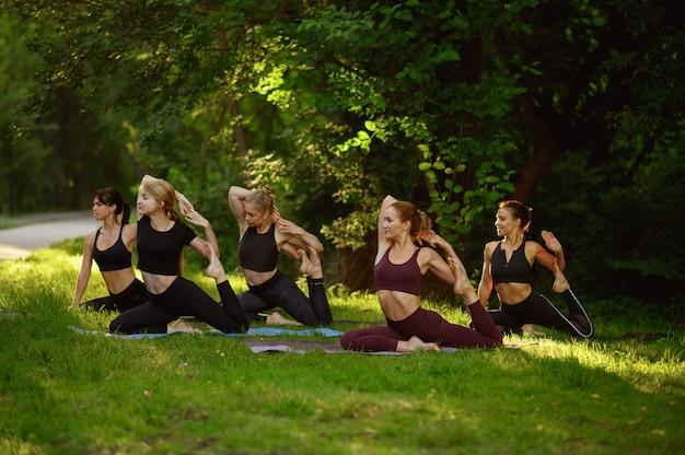 Mujeres haciendo ejercicios de estiramiento, entrenamiento de yoga en grupo sobre el césped en el parque