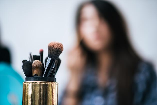Mujeres haciendo maquillaje con cepillo y cosmetica.