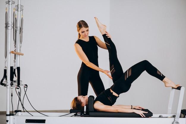 Mujeres haciendo pilates en un reformador.