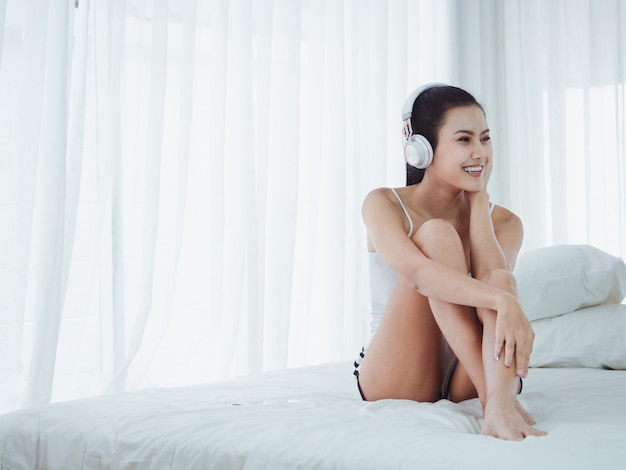 Mujeres hermosas asiáticas escuchando música en la cama, relajarse y felices en vacaciones
