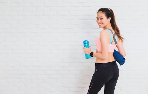 Mujeres hermosas asiáticas que sostienen la botella de agua y la estera de yoga después de jugar yoga y ejercicio en blanco