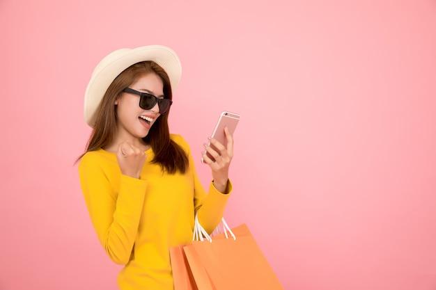 Mujeres hermosas compran en verano con bolsas de papel azul.