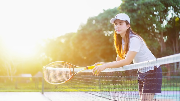 Mujeres hermosas de los deportes que se relajan felices con con la raqueta en el tenis