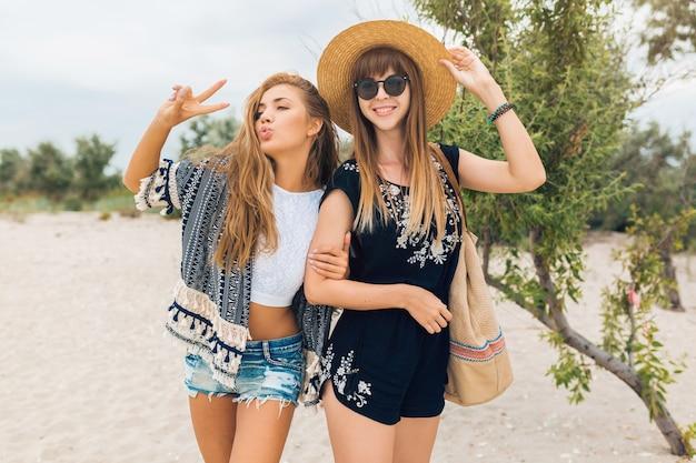 Mujeres hermosas con estilo en las vacaciones de verano en la playa tropical, estilo bohemio, amigos juntos, accesorios de moda, sonriente, emoción feliz, estado de ánimo positivo, pantalones cortos, sombrero de paja, divertirse