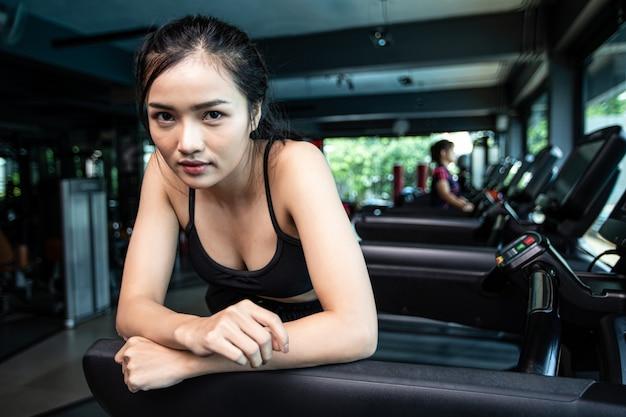 Mujeres hermosas fitness preparan para correr en la cinta en el gimnasio.