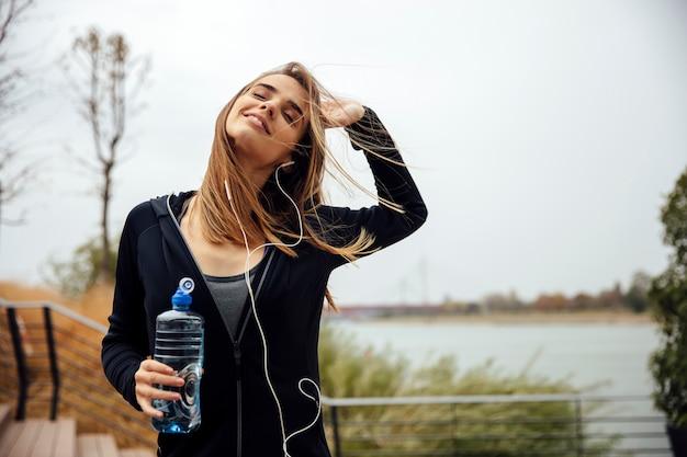 Mujeres hermosas jóvenes descansando y bebiendo agua después de hacer ejercicios.
