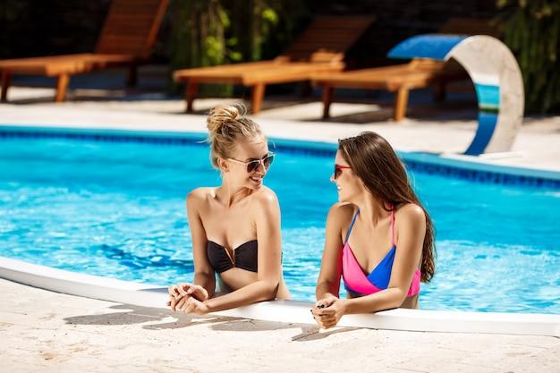 Mujeres hermosas jovenes que sonríen, que hablan, que se relajan en piscina.