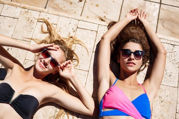 Mujeres hermosas jóvenes sonriendo, tomando el sol, relajarse junto a la piscina.
