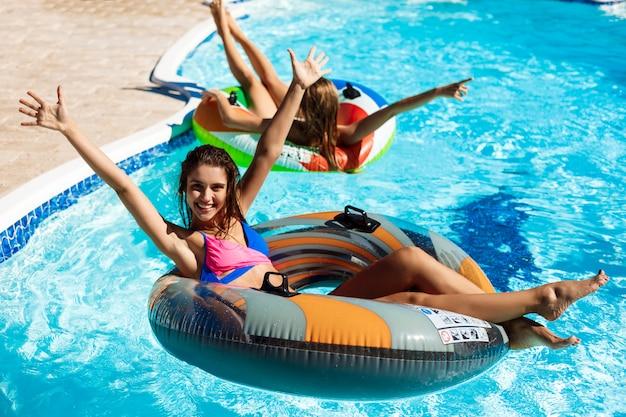 Mujeres hermosas jóvenes sonriendo, tomando el sol, relajarse, nadar en la piscina