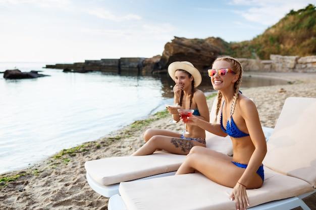 Mujeres hermosas jóvenes sonriendo, tomando el sol, tumbado en tumbonas cerca del mar