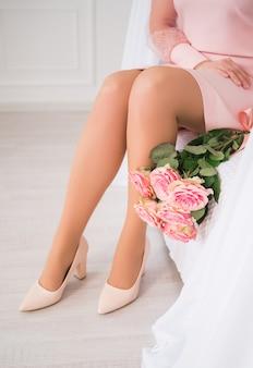 Mujeres hermosas piernas largas junto a flores color de rosa.