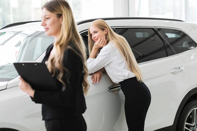 Mujeres hermosas en la sala de exposición de automóviles