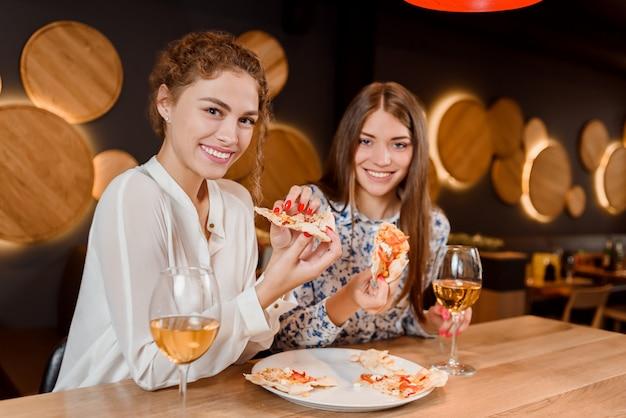 Mujeres hermosas sonriendo, posando y comiendo pizza en pizzería.
