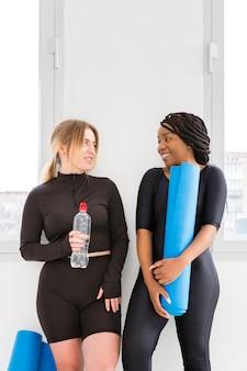 Mujeres hidratantes después de la clase de gimnasia