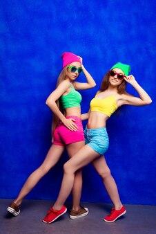 Mujeres hipster bastante cool posando con gorras y gafas