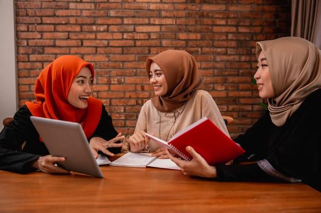 Mujeres hiyab conversando con amigos sobre tareas universitarias
