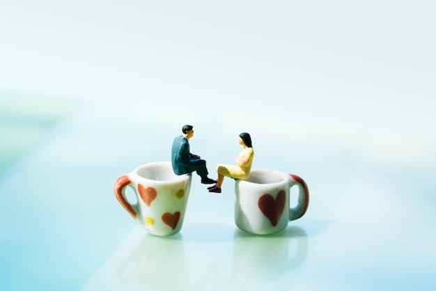 Mujeres y un hombre enamorado en la taza de café con el espacio de la copia.