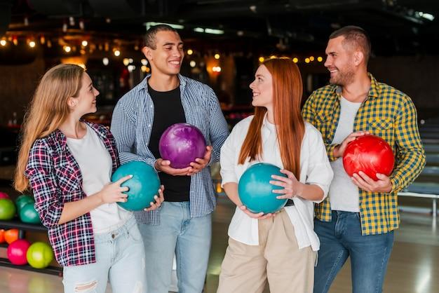 Mujeres y hombres jóvenes con coloridas bolas de boliche