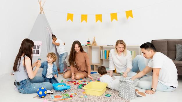 Mujeres y hombres jugando con niños en casa