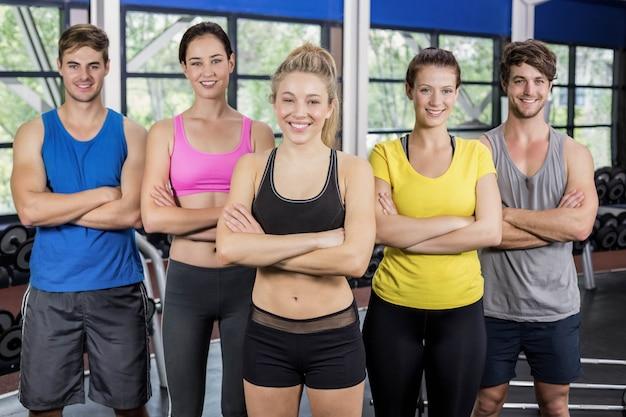 Mujeres y hombres sonrientes atléticos que presentan en el gimnasio del crossfit