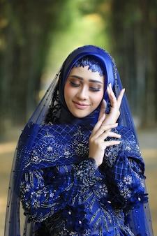 Las mujeres indonesias visten ropa nupcial musulmana tradicional al aire libre